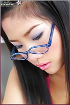 pensive look downwards wearing blue glasses pink lips parted