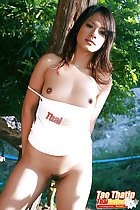 Standing against tree small breasts exposed trimmed pussy hair thighs parted