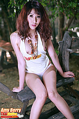 Seated On Rocking Horse Hands Down By Her Sides Long Hair Necklace Dangling Between Her Breasts Knees Pressed Together