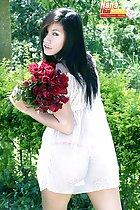 Looking over her shoulder long hair holding roses wearing white transparent dress in thong panties