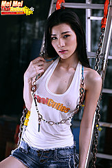 Standing Against Metal Ladder Wrapped In Chains Wearing White Top In Denim Shorts