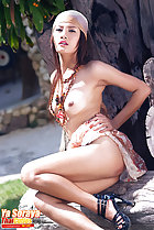 Ya Soraya seated topless with hand on hip bare breasts high heels