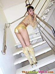 Standing On Stairs Looking Back Bending Over In Gold Hotpants Wearing Boots