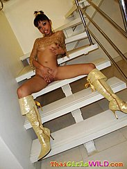 Seated Naked On Stairs Cupping Small Breasts Spreading Her Legs Hand Between Her Legs On Her Shaved Pussy Wearing High Heeled Boots