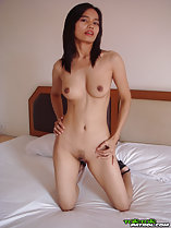 Kneeling nude on bed hands on hips small breasts trimmed pussy hair